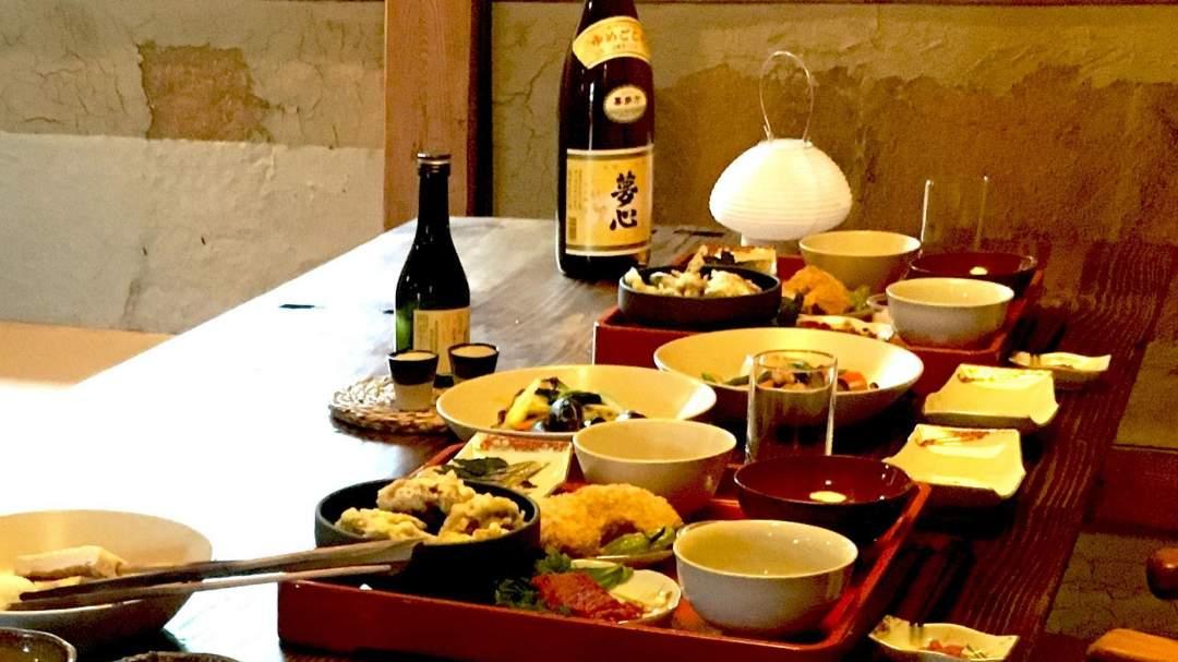 """奥川郷・御もてなし夜膳: 近くのお母さんたちによる郷土食のケータリングです。御膳には地元の食材をふんだんに使った郷土食、炊飯器には奥川のコシヒカリ(日本屈指の食味)、鍋には汁物をお届けします。""""暮らすように泊まる""""というコンセプトの宿ですので、夕方、近所からのお裾分けが届くようなイメージでのケータリングとなります。"""